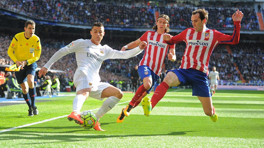 MADRID, SPAIN - FEBRUARY 27:   Cristiano Ronaldo of Real Madrid crosses the ball while being challenged by Diego Godin and Felipe Luis of Club Atletico de Madridduring the La Liga match between Real Madrid CF and Club Atletico de Madrid at Estadio Santiago Bernabeu on February 27, 2016 in Madrid, Spain.  (Photo by Denis Doyle/Getty Images)